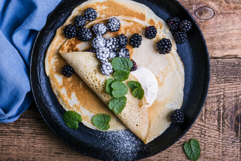 Delicious summer treat, healthy vegetarian breakfast with crepes, fresh blackberries and sour cream served in rural cast iron skillet, top view